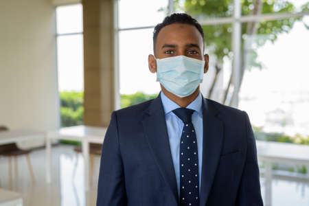 African businessman with surgical medical mask for protection at office Archivio Fotografico - 165337820