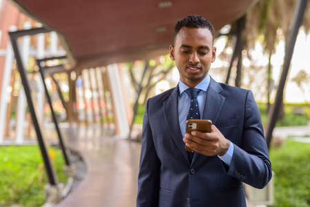 Portrait of handsome young African businessman smiling and using mobile phone