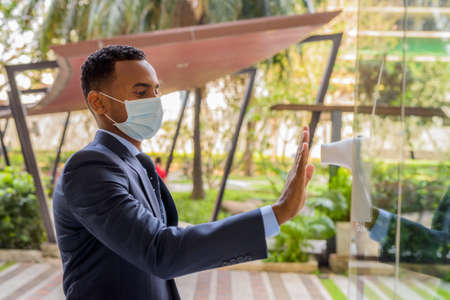 African businessman with surgical medical mask for protection measuring body temperature before entering building