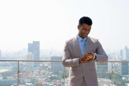 Portrait of handsome young African businessman wearing suit checking time from wrist watch