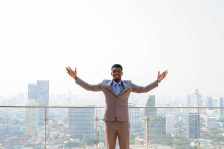 Portrait of handsome young African businessman wearing suit with arms crossed while smiling against rooftop city view Banco de Imagens