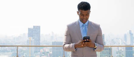 Portrait of handsome young African businessman wearing suit while smiling and using mobile phone