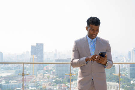 Portrait of handsome young African businessman wearing suit smiling and texting with mobile phone