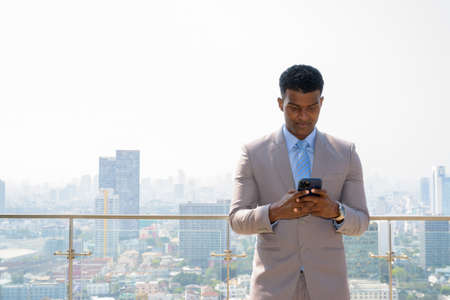 Portrait of handsome young African businessman wearing suit and using mobile phone
