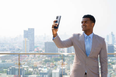 Portrait of handsome young African businessman wearing suit and taking selfie with mobile phone while smiling