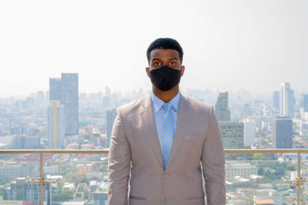 African businessman with face mask for protection at rooftop