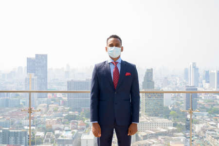 African businessman with surgical medical mask for protection against city view