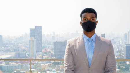 African businessman with face mask for protection at rooftop looking at camera