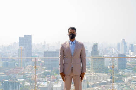 African businessman with face mask for protection at rooftop against city view