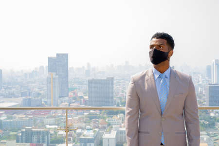 African businessman with face mask for protection at rooftop thinking