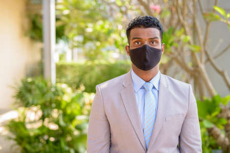 African businessman with face mask for protection outdoors looking at camera