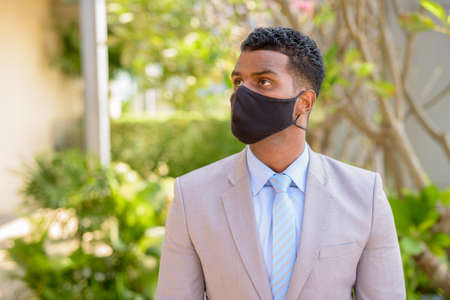 African businessman with face mask for protection outdoors thinking