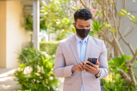 African businessman with face mask for protection using mobile phone Banco de Imagens