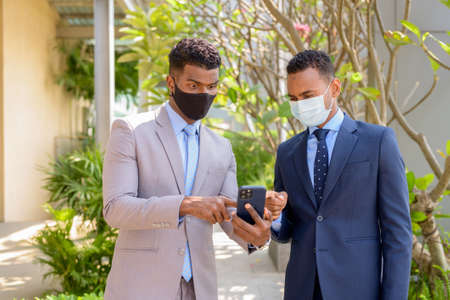 Two African businessman with face mask for protection using mobile phone Banco de Imagens