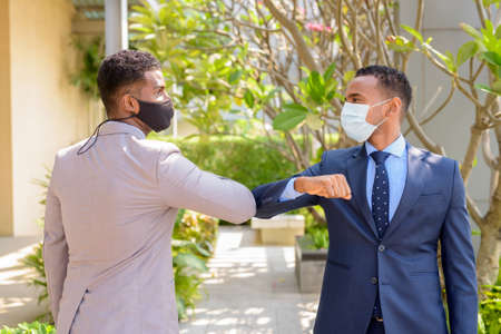 Two African businessman wearing medical mask while greeting with elbow bump greeting. Social distance concept