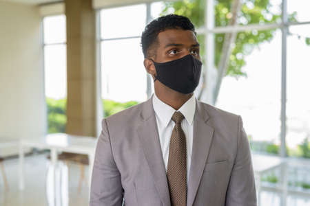 Portrait of African businessman with surgical medical mask for protection thinking at office Banco de Imagens