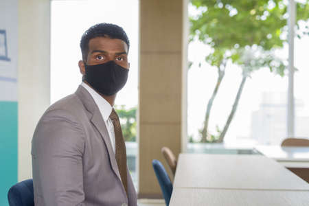 African businessman with face mask for protection sitting at office