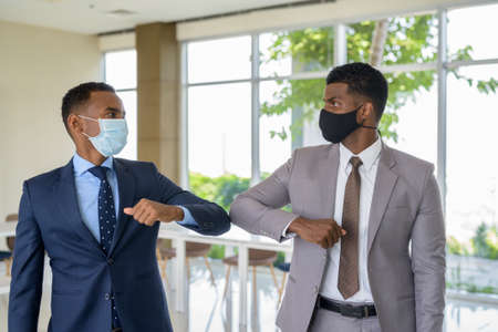 Two African businessman wearing medical mask while greeting with elbow bump greeting at office. Social distance concept during the coronavirus epidemic.