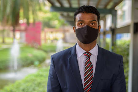 Confident African businessman with face mask for protection outdoors looking at camera