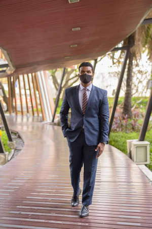 African businessman walking outdoors while wearing face mask for protection full length shot Archivio Fotografico - 164395054