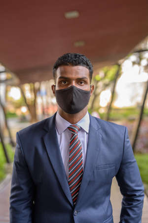 Confident African businessman with face mask for protection outdoors looking at camera vertical shot Banco de Imagens