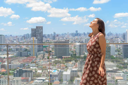 Portrait of beautiful woman relaxing outdoors at rooftop with city view