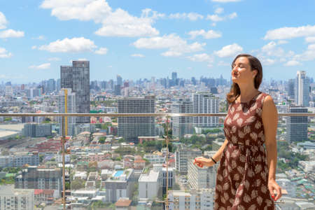 Portrait of beautiful woman enjoying sun with eyes closed outdoors at rooftop with city view