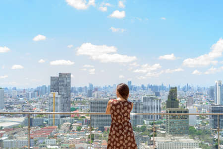 Back view of woman outdoors at rooftop with city view