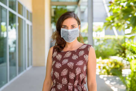 Woman wearing protective face mask against virus outdoors in quarantine and looking at camera 스톡 콘텐츠
