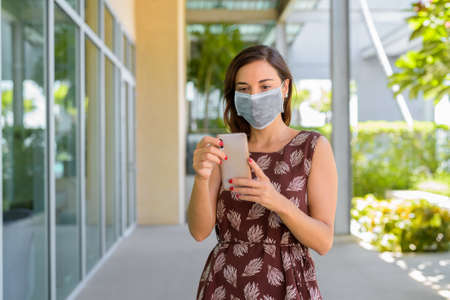 Woman wearing protective face mask against virus outdoors in quarantine while using phone