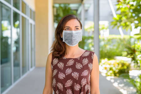 Woman wearing protective face mask against virus outdoors in quarantine and thinking 스톡 콘텐츠