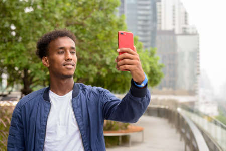 Portrait of handsome black African man at rooftop garden