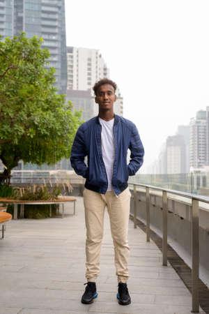 Full length shot of handsome black African man at rooftop garden