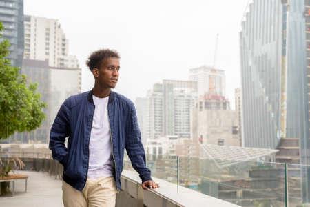 Portrait of handsome black African man at rooftop garden thinking