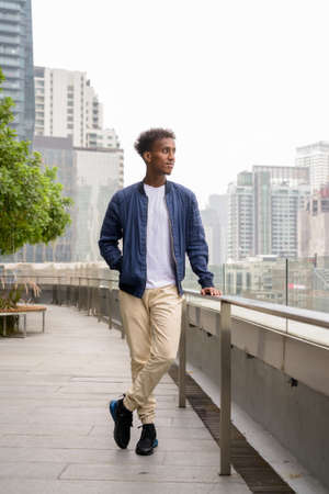 Full body shot of handsome black African man thinking at rooftop garden 스톡 콘텐츠