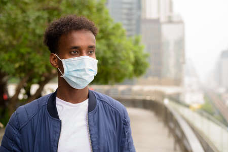 Handsome black African man wearing face mask and thinking