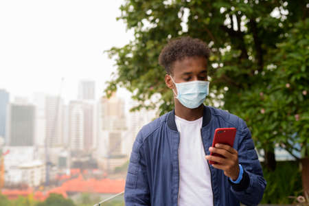 African man wearing face mask to protect against virus while using phone 스톡 콘텐츠