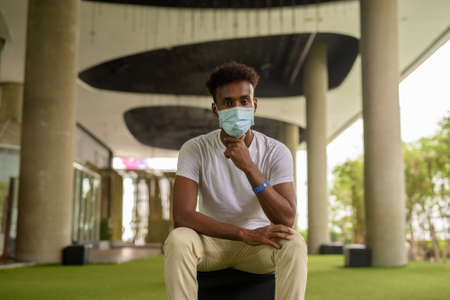 Portrait of handsome black African man sitting wearing face mask while thinking