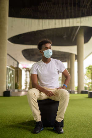 Full length shot of handsome black African man sitting wearing face mask while thinking