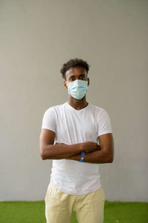 African man wearing face mask against plain wall background with arms crossed