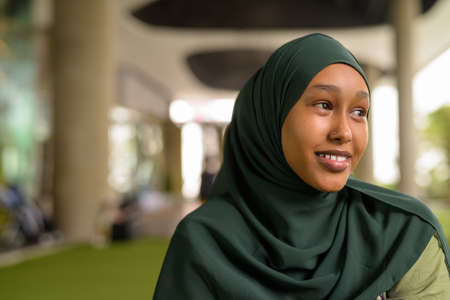 Portrait of beautiful black African Muslim woman smiling and thinking outdoors