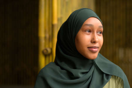 Portrait of beautiful black African Muslim woman outdoors thinking and looking confident