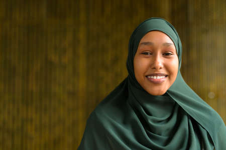 Portrait of beautiful black African Muslim woman smiling outdoors 스톡 콘텐츠