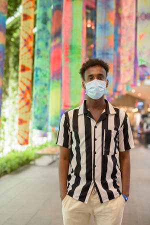 Portrait of handsome black African man wearing face mask in shopping mall