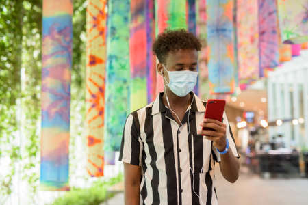 Portrait of handsome black African man wearing face mask in shopping mall while using mobile phone 스톡 콘텐츠
