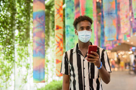 African man wearing face mask in shopping mall while using mobile phone and thinking 스톡 콘텐츠