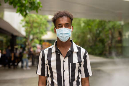 Portrait of handsome black African man wearing face mask outdoors in shopping mall