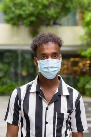 African man wearing face mask against coronavirus outdoors in shopping mall
