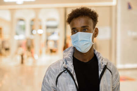 Portrait of handsome black African man wearing face mask in shopping mall while thinking
