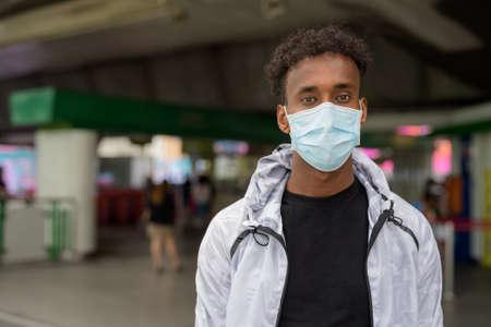 Portrait of handsome black African man wearing face mask at train station